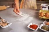 Motion blurred closeup on housewife sprinkling flour on table — Stock Photo