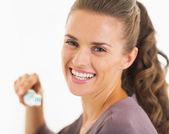 Uśmiechnięta młoda kobieta trzymając szczoteczkę do zębów z pasty do zębów — Zdjęcie stockowe