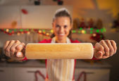 Closeup on young housewife showing rolling pin — Stockfoto