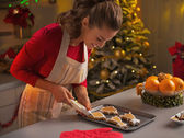 Happy young housewife decorating christmas cookies with glaze — Stock Photo