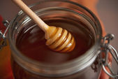 Closeup on honey dipper in honey jar — Stock Photo