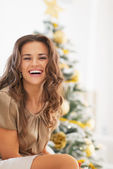 Smiling young woman sitting in front of christmas tree — Stock Photo
