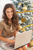 Portrait of happy young woman using laptop near christmas tree — Stock Photo