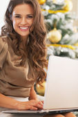 Portrait of smiling young woman using laptop near christmas tree — Stock Photo