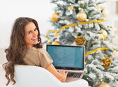 Smiling young woman using laptop near christmas tree — Stock Photo