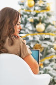 Portrait of thoughtful young woman with laptop in front of christmas tree — Foto Stock