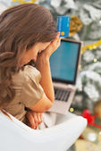 Stressed young woman with credit card and laptop — Stock Photo