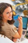 Portrait of smiling young woman with credit card using laptop — Foto Stock