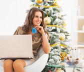 Portrait d'une femme jeune réfléchie avec carte de crédit à l'aide d'ordinateur portable — Photo