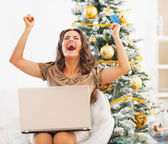Happy young woman with credit card and laptop rejoicing — Stock Photo