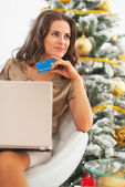 Thoughtful young woman with credit card and laptop near christma tree — Stock Photo