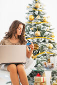 Young woman making online shopping near christmas tree — Stock Photo