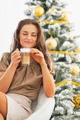 Young woman enjoying latte macchiato in front of christmas tree — Stock Photo