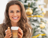 Smiling young woman with latte macchiato near christmas tree — Stock Photo