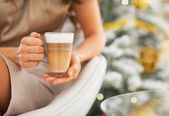 Latte macchiato in hand of woman in front of christmas tree — Foto Stock