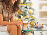 Woman having latte macchiato and candies near christmas tree — Stock Photo