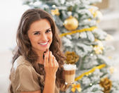 Woman eating candy with latte macchiato near christmas tree — Stock Photo