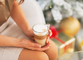 Closeup on latte macchiato in hand of woman sitting near christmas tree — Foto Stock