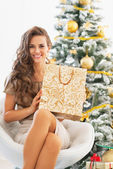 Happy young woman with shopping bag near christmas tree — Stockfoto