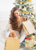 Smiling young woman with shopping bags near christmas tree — Foto Stock