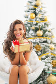 Woman with christmas present box near christmas tree — Stock Photo