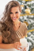 Portrait of happy young woman lighting candle near christmas tree — Stock Photo