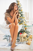 Thoughtful young woman sitting in front of christmas tree — Stock Photo