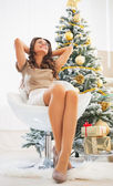 Relaxed young woman sitting in front of christmas tree — Stock Photo