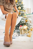 Closeup on woman sitting near christmas tree — Stock Photo