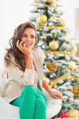 Thoughtful young woman sitting in front of christmas tree — Stok fotoğraf