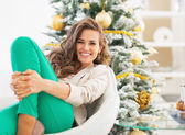 Portrait of happy young woman relaxing near christmas tree — Stok fotoğraf