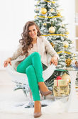 Full length portrait of happy young woman near christmas tree — Stok fotoğraf