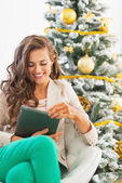 Happy young woman using tablet pc near christmas tree — Stock Photo