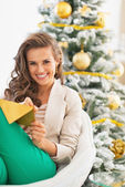Happy young woman writing on envelope near christmas tree — Stock Photo