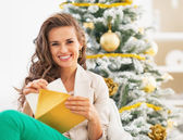 Woman putting postcard into envelope near christmas tree — Foto de Stock