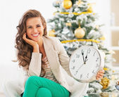 Happy young woman showing clock in front of christmas tree — Stock Photo