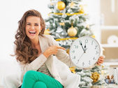 Happy young woman pointing on clock in front of christmas tree — Stock Photo