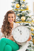 Portrait of smiling young woman showing clock in front of christmas tree — Stock Photo