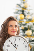 Thoughtful young woman showing clock in front of christmas tree — Stock Photo