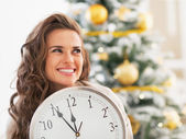 Woman with clock looking on copy space in front of christmas tree — Stock Photo