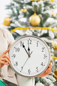 Closeup on clock in hand of woman in front of christmas tree — Stock Photo