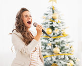 Happy young woman singing near christmas tree — Stok fotoğraf