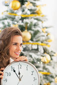 Happy young woman with clock in front of christmas tree — Foto Stock