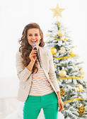 Happy young woman singing in front of christmas tree — Stok fotoğraf