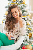 クリスマスの木の近くのテレビのリモコンを使用して幸せな若い女 — ストック写真