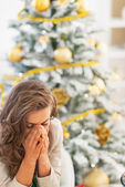 Stressed young woman sitting in front of christmas tree — Stock Photo