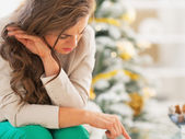 Stressed young woman in front of christmas tree — Stock Photo