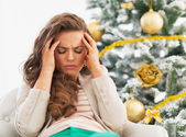Portrait of frustrated young woman near christmas tree — Stock Photo