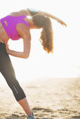 Fitness young woman stretching on beach — Stock Photo