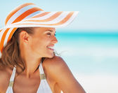 Portrait of happy young woman in swimsuit and beach hat looking — Photo